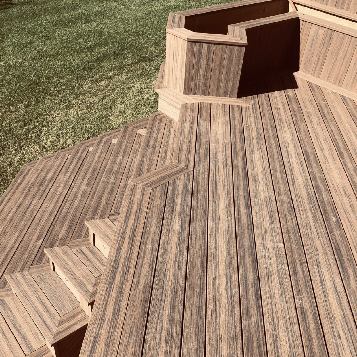Deck design ideas incorporating planters and stairs using composite decking materials